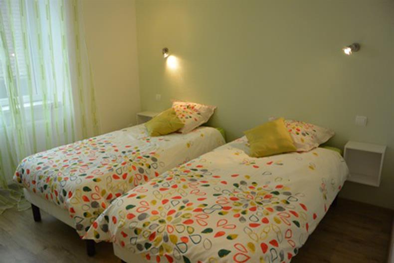 Chambre verte, deux couchages individuels.